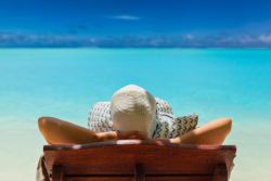 Girl lays on lounge chair on the beach