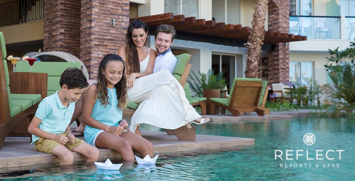 Family floats paper boats in luxury resort pool
