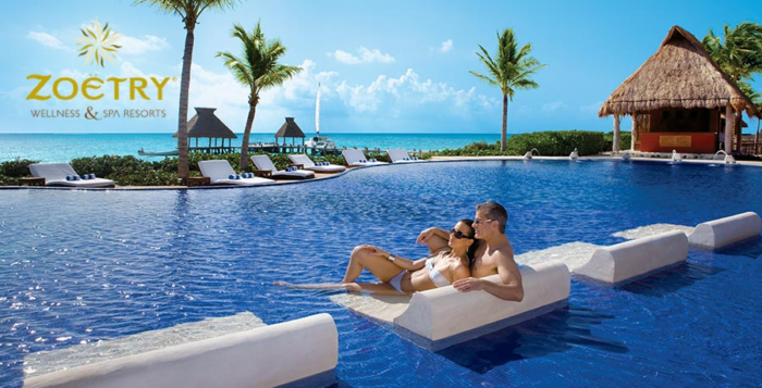 A couple relaxes on in-pool seating at a resort
