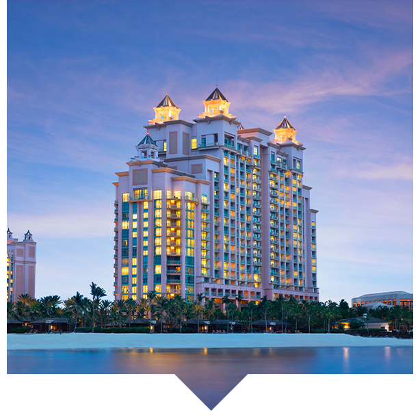 Grand resort  with lit towers next to the ocean